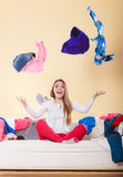 Happy woman on sofa in messy room throwing clothes Royalty Free Stock Photo