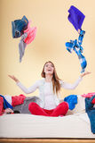 Happy woman on sofa in messy room throwing clothes Royalty Free Stock Images