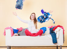 Happy woman on sofa in messy room throwing clothes Stock Photography