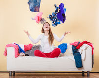 Happy woman on sofa in messy room throwing clothes Royalty Free Stock Image