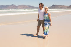Happy woman and son walking on shore. At beach royalty free stock photo