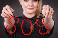Happy woman with sos sign. Help concept. Young blonde smiling woman with red sos symbol sign. Happy female helper offering support Royalty Free Stock Photo