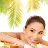 Happy woman at spa. Closeup portrait of happy woman lying down on massage table on tropical beach in sunny day, enjoying day spa, relaxation outdoors, beauty Stock Photography