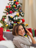 Happy woman speaking mobile near Christmas tree Stock Photo