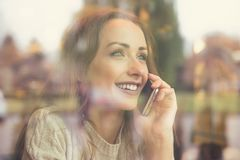 Happy woman speaking on phone in cafe Stock Images