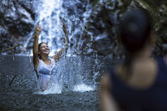 Happy  woman splashing in the water near the waterfall. Stock Photos