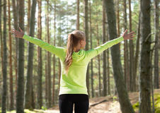 Happy woman in sport clothes raising hands Stock Images