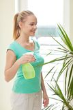 Happy woman in spraying houseplants at home Royalty Free Stock Image