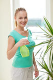 Happy woman in spraying houseplants at home Stock Images