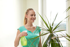 Happy woman in spraying houseplants at home Stock Photo