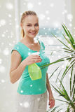 Happy woman in spraying houseplants at home Stock Image