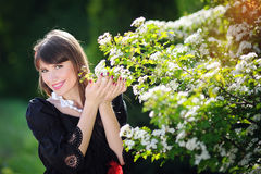 Happy woman in a spring garden holding flowers Stock Photography