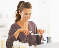 Happy woman squeezing toothpaste from tube Stock Images