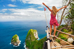 Happy woman stand at high cliff viewpoint, look at sea. Family vacation lifestyle. Happy woman with raised in air hand stand at viewpoint. Look at beautiful Royalty Free Stock Image