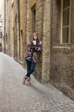 Happy woman is standing in an alley in historic city Stock Image