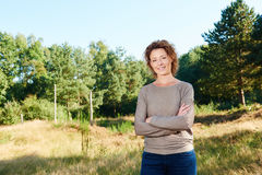 Happy woman standing with arms crossed in park Stock Photos