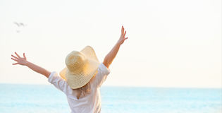 Happy woman standing arms outstretched back and enjoy life on be Stock Photos