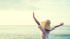 Happy woman standing arms outstretched back and enjoy life on be Stock Image