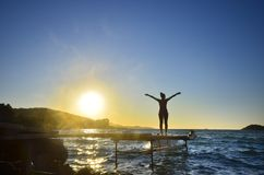 Happy woman standing arms outstretched back and enjoy life on the beach pier at sunset. Happy woman standing arms outstretched back and enjoy life on the beach Royalty Free Stock Photography