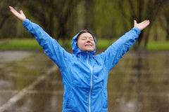Happy woman standing with arms outstretched in rain. Royalty Free Stock Image