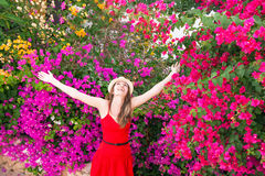 Happy woman is standing among beautiful colorful flowers. Stock Photo