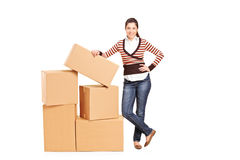 Happy woman standing by a bunch of boxes Royalty Free Stock Photography
