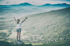 Happy woman standing on a cliffs edge. Instagram stylization Royalty Free Stock Photo
