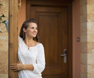 Happy woman standing on doorstep Stock Images