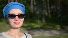 Happy woman standing in the forest near beach in turban and sunglasses looking forward and smiling. stock video footage