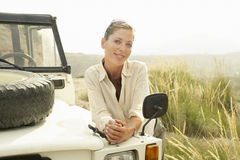 Happy Woman Standing By Four-Wheel-Drive Car Royalty Free Stock Images