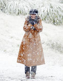 Happy woman standing in fresh falling white snow Stock Photos