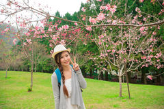 Happy woman standing in front of cherry tree Royalty Free Stock Photos