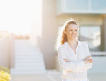 Happy woman standing in front of house building Stock Images