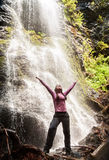 Happy woman standing in front of waterfall Stock Photos