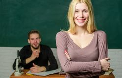 Happy woman standing hands crossed in classroom with teacher. Female student with schoolmaster at examination. High. School student answering at seminar royalty free stock images