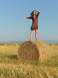 Happy woman standing on a hay stack Royalty Free Stock Photo