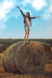Happy woman standing on haystack Stock Image