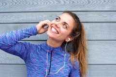 Happy woman standing with headphones listening to song Royalty Free Stock Photography