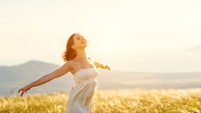 Happy woman standing with her back on sunset in nature iwith ope royalty free stock image