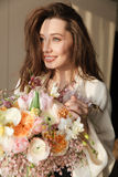 Happy woman standing and holding bouquet of flowers at home. Happy attractive young woman in bathrobe standing and holding bouquet of flowers at home royalty free stock image
