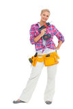 Happy woman standing holding a drill Royalty Free Stock Images