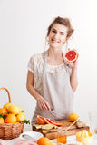 Happy woman standing indoors near table with a lot of citruses Royalty Free Stock Image