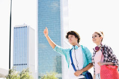Happy woman standing with male friend hailing a taxi in city. Happy women standing with male friend hailing a taxi in city Royalty Free Stock Photos