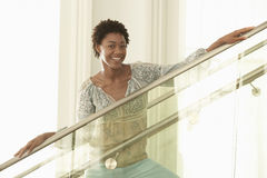 Happy Woman Standing On Modern Glass Stairs. Portrait of happy young African American woman standing on modern glass stairs Stock Photography