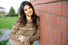 Happy woman standing near brick wall Stock Image