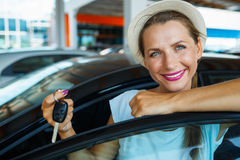 Happy woman standing near a car with keys in hand - concept of b Stock Photos