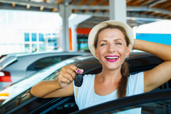 Happy woman standing near a car with keys in hand - concept of b Stock Image