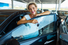Happy woman standing near a car with keys in hand - concept of b Stock Photography