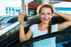 Happy woman standing near a car with keys in hand - concept of b Stock Photo