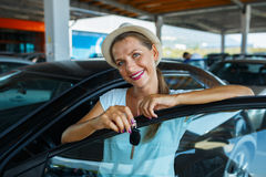 Happy woman standing near a car with keys in hand - concept of b Royalty Free Stock Photography